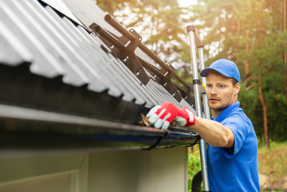 Man Clearing Gutters - Best Types Of Guttering